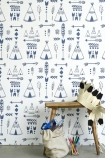 lifestyle image of Hibou Home Teepees, A Tribal Gathering Children's Wallpaper - Indigo/White with wooden side table with paper crown and bag of toys
