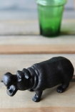 lifestyle image of Hippo Bottle Opener on wooden table with green glass in background