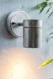lifestyle image of St Ives Hot Dipped Down Wall Light - Small lit up with bamboo plant and pale grey wall background