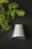 lifestyle image of St Ives Hot Dipped Funnel Wall Light on dark grey wall and plant in foreground