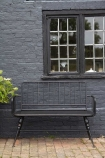 Lifestyle image of the Industrial-Style Black Metal Two-Seater Bench in an outdoor setting