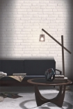 lifestyle image of Koziel White Brick Wallpaper with dark grey sofa and floor lap and round wooden coffee table