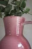 Close-up lifestyle image of the Tall Pink Glazed Jug Style Vase With Handle with faux stems