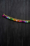 Panned out image of the Large Rainbow Baubles & Tinsel Garland in a row