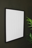 angled lifestyle image of Large Black Wooden Frame - 30cm X 40cm with plant on dark grey wall background