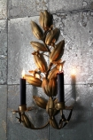 Lifestyle image of Leaf Wall Candle Holder lit up on grey silver tile wallpaper