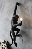 lifestyle image of Left-Hand Hanging Monkey Wall Lamp - Black - Suitable For Outdoors lit up on grey wall with black and white cowhide armchair in background
