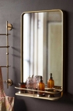 Lifestyle image of the Light Gold Tall Bathroom Mirror With Shelf with bathroom accessories in shelf and hooks in background on dark wall background