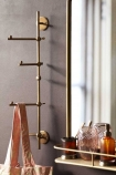 Lifestyle image of the Light Gold Vertical Coat Rack With Swivelling Pegs with pink tote bag hanging from peg and mirror with shelf in background on dark wall