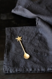 lifestyle image of Linen Napkin Set - Black with gold star spoon on black table