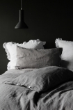 lifestyle image of Lisbon Soft Linen Pair Of Pillowcases - Grey with grey duvet and white pillows with black ceiling light and dark grey wall background