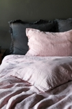 lifestyle image of Lisbon Soft Linen Pair Of Pillowcases - Rose Pink on bed with pink duvet and grey pillows and grey wall abckground