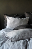 lifestyle image of Lisbon Soft Linen Pair Of Pillowcases - Silver Grey with grey duvet and grey pillows with dark grey wall background
