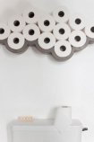 lifestyle image of Concrete cloud toilet roll shelf above a toilet full of toilet roll above toilet and filled with toilet rolls on white wall background