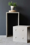 lifestyle image of Lyon Beton Concrete Dice StoolTable - Available In 2 Sizes one in front of the other with small plant in pot on top and dark wall background