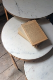 Round Nest Of 3 Marble Side Tables on pale wooden florring and vintage book detail image