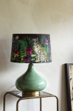 Lifestyle Image of Matthew Williamson Midnight Jungle Table Lamp & Shade on gold side table with pale wall background