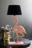 lifestyle image of Metal Coral Flamingo Table Lamp with dark blue velvet shade on black side table with plant in gold pot