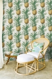 lifestyle image of Mind The Gap Ananas Wallpaper with rattan chair and foot stool with white and tropical print cushions