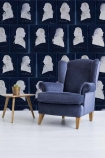 lifestyle image of Mind The Gap Dutch Blauw Collection - Dutch Portraits Wallpaper - Blue with blue armchair and wooden side table