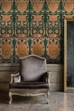 Lifestyle image of Fontainebleau wallpaper in anthracite with a grey velvet chair in front of it and reflective grey flooring