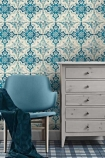 lifestyle image of Mind The Gap Mediterraneo Collection - Longwy Wallpaper with blue chair with blue balnet on top and grey chest of drawers