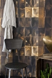 Lifestyle image of the Shibui wallpaper in copper in bathroom with black chair and white robe hanging on wall