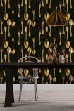 lifestyle image of Mind The Gap The Antiquerian - Cutlery Wallpaper - Brass with black table and metal with chair with gold ceiling light above