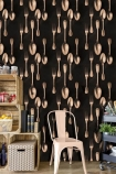 lifestyle image of Mind The Gap The Antiquerian - Cutlery Wallpaper - Copper with wooden shelf unit filled with ornaments and a striped storage box and white chair