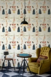 lifestyle image of Mind The Gap The Great Show Wallpaper with mustard yellow armchair and wooden and blue side table with small chair
