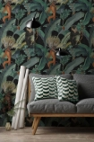 lifestyle image of Mind The Gap The Rediscovered Paradise - Bermuda Wallpaper with grey sofa with green patterned cushions and rolled posters