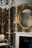 lifestyle image of Mind The Gap The World Of Antiquity - Gardens of Pompeii Wallpaper with black and white fireplace under round wall mirror and white chair