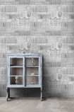 lifestyle image of Mind The Gap Vitruvius Wallpaper - 2 Colours Available with small grey glass door cabinet