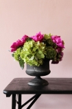 lifestyle image of Mixed Floral Arrangement In Grey Pot on black table and pink wall background