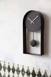 Lifestyle image of the Modern Black & Brass Pendulum Clock on pale wall with patterned wallpaper background