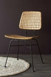 Lifestyle image of the natural Modern Woven Rattan Dining Chair facing forwards on mandala rug and wooden flooring with dark wall background
