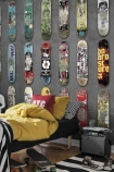 Lifestyle image of Mr Perswall Wallpaper - Adventure Collection - Line Up Skateboards in kids bedroom with single bed and yellow bedding with aux speaker in corner
