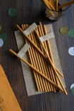 Lifestyle image of the Pack Of 20 Mustard Gold Paper Straws With Gold Glitter Tags