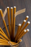 Image from above of the Pack Of 20 Mustard Gold Paper Straws With Gold Glitter Tags in a glass
