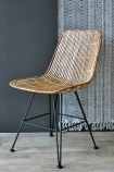 Blonde Rattan Dining Chair on grey background lifestyle image