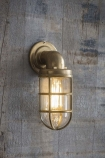 Lifestyle image of the Nautical Inspired Brass Bulkhead Down Wall Light lit up on grey wooden wall background