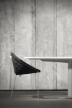 lifestyle image of NLXL CON-03 Concrete Wallpaper by Piet Boon with black chair at round white dining table