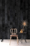 lifestyle image of NLXL PHM-35 Burnt Wood Wallpaper By Piet Hein Eek with wooden chair and black side table with gold ornaments on