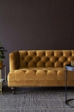 Lifestyle image of Ochre Gold Velvet Chesterfield Sofa with grey rug flooring and dark wall background