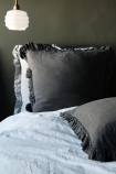 lifestyle image of Olivia Soft Linen Frill Cushion - Slate Grey on bed with white duvet and ceiling light and grey wall background