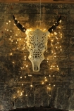 lifestyle image of Ornate Metal Faux Bull Skull With Horns - White covered in fairy lights on brick wall background