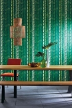 lifestyle image of Osborne & Little Bamboo Wallpaper - 6 Colours Available wooden bench table with plant in green vase and orange chair with rattan ceiling light above