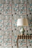 lifestyle image of Osborne & Little Curio Wallpaper with wooden desk and blue and white table lamp