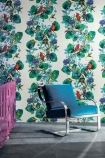lifestyle image of Osborne & Little Rain Forest Wallpaper - 2 Colours Available with blue velvet chair and pink chair on grey flooring
