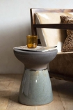 Lifestyle image of the Pablo Dipped Black Stool with amber glass on top and armchair in background on wooden flooring